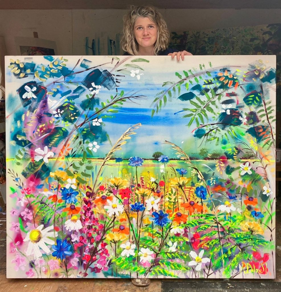 Artist Rachael Dalzell with one of her signature bright and cheerful landscape paintings